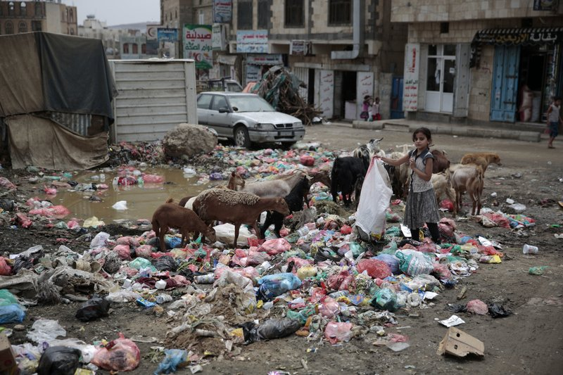 FILE - In this July 26, 2017 file photo, a girl scavenges for recyclable items at a garbage dump in a street in Sanaa, Yemen. (AP Photo/Hani Mohammed, File)