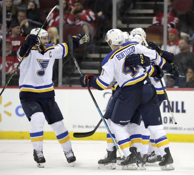 St. Louis Blues players celebrate an overtime goal by Vince Dunn (29) during an NHL hockey game against the New Jersey Devils, Saturday, March 30, 2019, in Newark, N. (AP Photo/Julio Cortez)