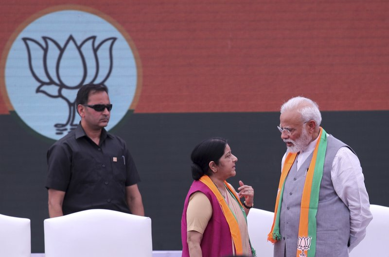Indian Prime Minister Narendra Modi, right, talks to Foreign Minister Susuhma Swaraj during the release BJP's manifesto for the upcoming general elections in New Delhi, India, Monday, April 8, 2019. (AP Photo/Manish Swarup)
