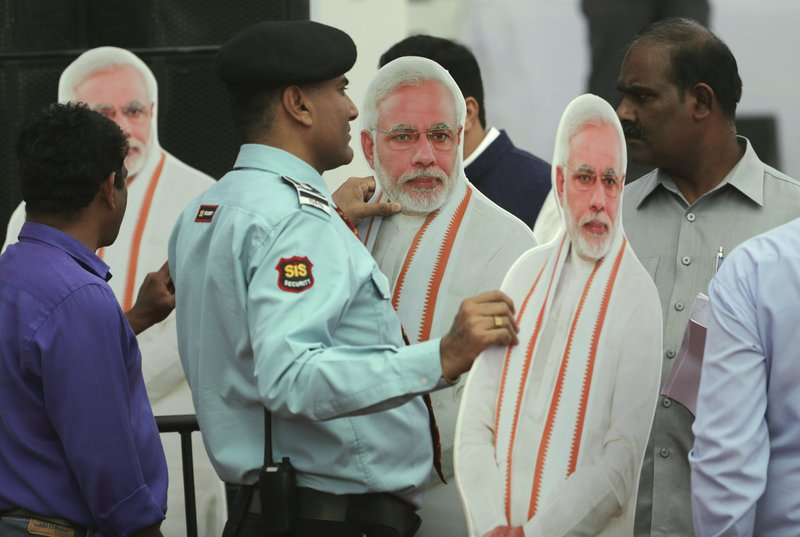 A private security guard stands holding cut-outs of Indian Prime Minister Narendra Modi, to be placed during a function to release Bharatiya Janata Party or BJP's manifesto for the upcoming general elections in New Delhi, India, Monday, April 8, 2019. (AP Photo/Manish Swarup)