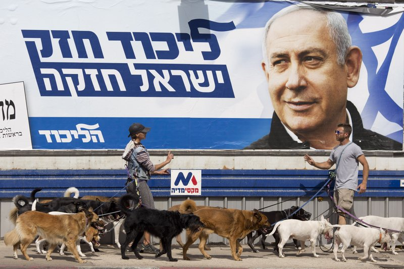 Dog walkers argue as they pass by an election campaign billboard shows Israeli Prime Minister Benjamin Netanyahu in Tel Aviv, Israel, Monday, April 8, 2019. (AP Photo/Ariel Schalit)
