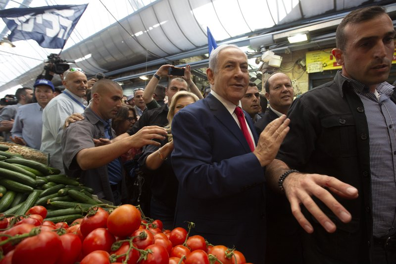 Israeli Prime Minister Benjamin Netanyahu, center, escorted by bodyguards walks during a visit to the market on the eve of Israel's general elections in Jerusalem, Monday, April 8, 2019. (AP Photo/Sebastian Scheiner)