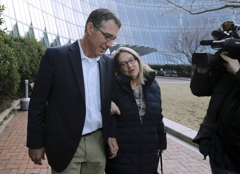 FILE - In this March 28, 2019 file photo, former Texas tennis coach Michael Center, left, departs federal court in Boston with an unidentified woman after facing charges in a nationwide college admissions bribery scandal. (AP Photo/Charles Krupa, File)