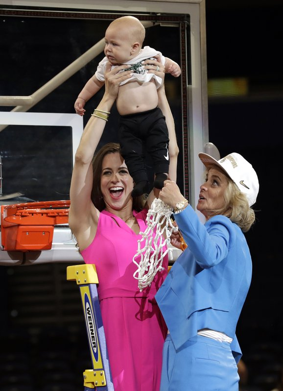 Baylor coach Kim Mulkey, right, watches as her daughter and assistant coach Makenzie Fuller holds up her 6-month-old son Kannon Reid Fuller, after the Final Four championship game against Notre Dame in the NCAA women's college basketball tournament Sunday, April 7, 2019, in Tampa, Fla. (AP Photo/Chris O'Meara)