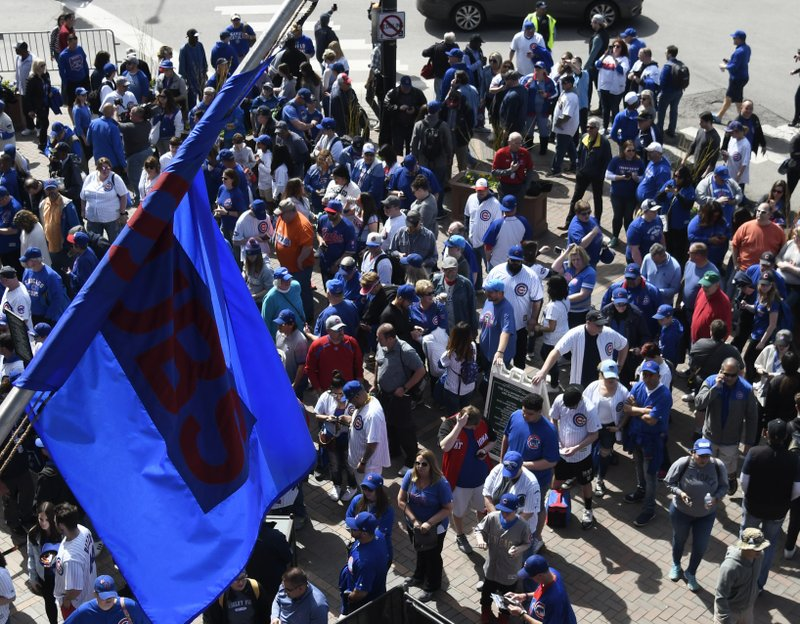 Fans wait to get inside the ballpark before the Chicago Cubs home opening baseball game against the Pittsburgh Pirates, Monday, April 8, 2019, in Chicago. (AP Photo/David Banks)