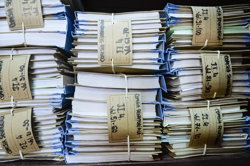 Files containing indictment papers for the 1989 anti-communist uprising are stacked for the media at the Public Ministry in Bucharest, Romania, Monday, April 8, 2019. (AP Photo/Andreea Alexandru)
