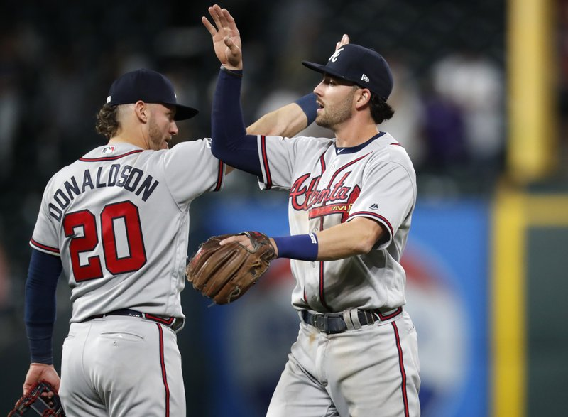 Atlanta Braves shortstop Dansby Swanson, front, is congratulated by third baseman Josh Donaldson after the Braves retired the Colorado Rockies in the ninth inning of a baseball game Monday, April 8, 2019, in Denver. (AP Photo/David Zalubowski)