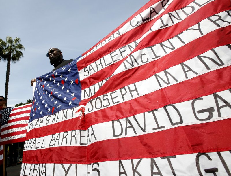 Malaki Seku Amen holds up an American flag with the names of people shot and killed by law enforcement officers, as he joins other in support of a bill that would restrict the use of deadly force by police, Monday, April 8, 2019, in Sacramento, Calif. (AP Photo/Rich Pedroncelli)