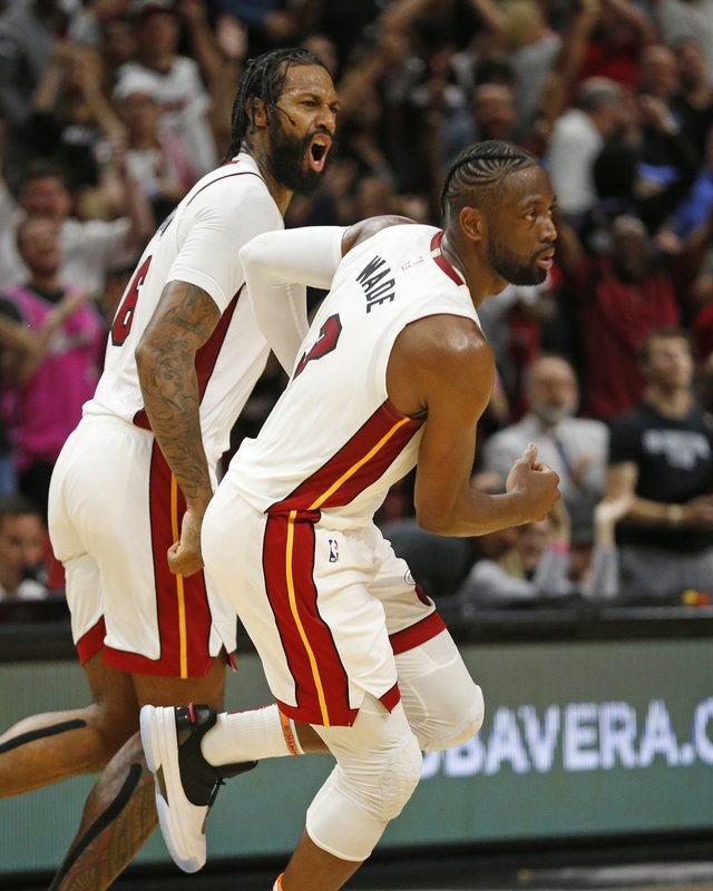Miami Heat forward James Johnson (16) and guard Dwyane Wade (3) run upcourt after Wade scored the final basket of an NBA basketball game against the Dallas Mavericks during the second half Thursday, March 28, 2019, in Miami. (AP Photo/Joel Auerbach)