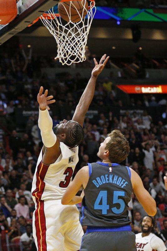 Miami Heat guard Dwyane Wade (3) scores the final basket of the game against Dallas Mavericks guard Ryan Broekhoff (45) during the second half of an NBA basketball game, Thursday, March 28, 2019, in Miami. (AP Photo/Joel Auerbach)