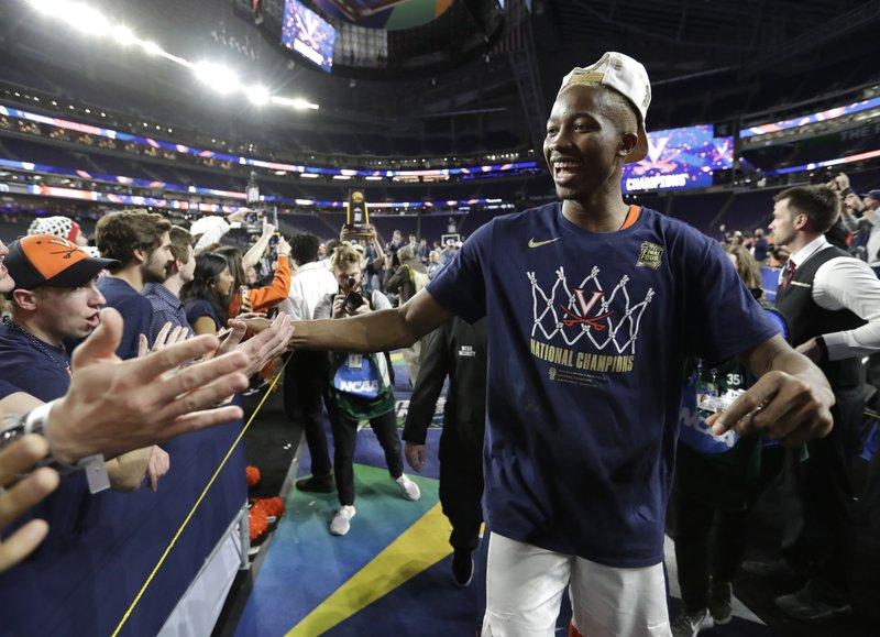 Virginia forward Mamadi Diakite celebrates with fans after the championship game against Texas Tech in the Final Four NCAA college basketball tournament, Monday, April 8, 2019, in Minneapolis. (AP Photo/David J. Phillip)