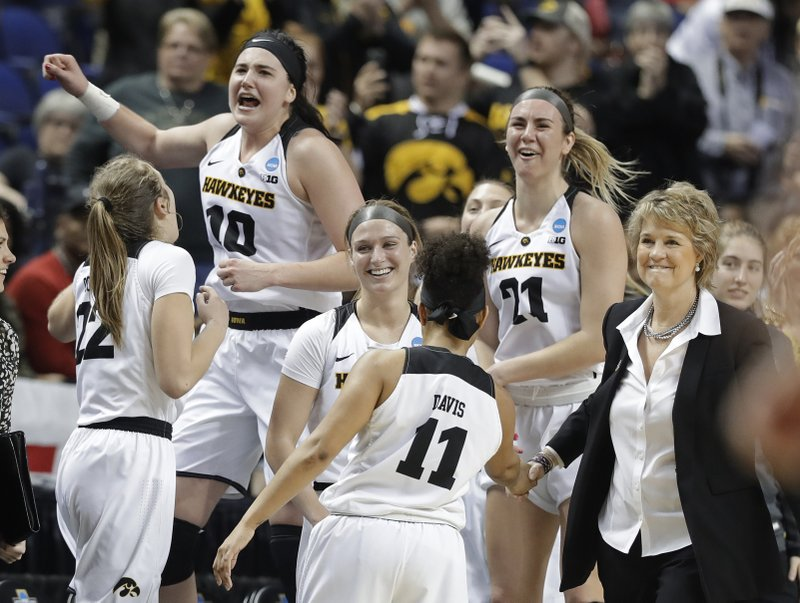 Iowa players including Megan Gustafson (10) and Hannah Stewart (21) celebrates in the closing seconds of the second half of a regional women's college basketball game against North Carolina State in the NCAA Tournament in Greensboro, N. (AP Photo/Chuck Burton)