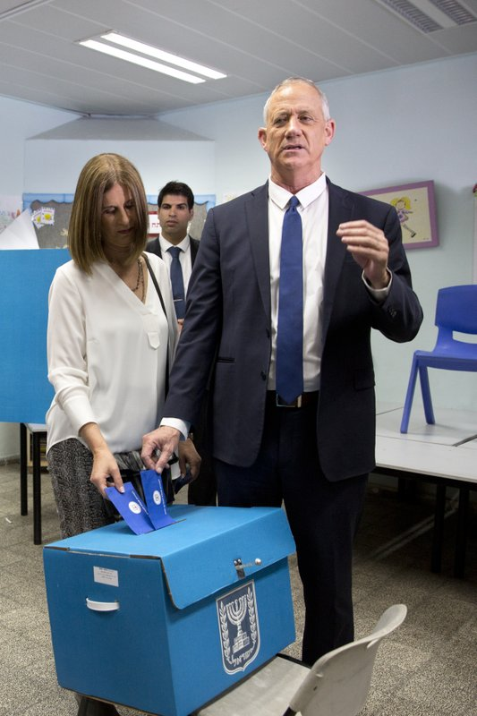 Blue and White party leader Benny Gantz, right, casts his vote with his wife Revital Gantz during Israel's parliamentary elections in Rosh Haayin, Israel, Tuesday, April 9, 2019. (AP Photo/Sebastian Scheiner)