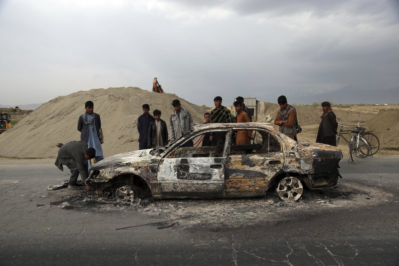 Afghans watch a civilian vehicle burnt after being shot by US forces following an attack near the Bagram Air Base, north of Kabul, Afghanistan, Tuesday, April 9, 2019. (AP Photo/Rahmat Gul)