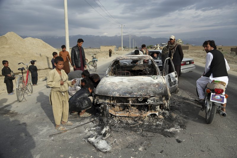 Afghans watch a civilian vehicle burnt after being shot by US forces after an attack near the Bagram Air Base, north of Kabul, Afghanistan, Tuesday, April 9, 2019. (AP Photo/Rahmat Gul)