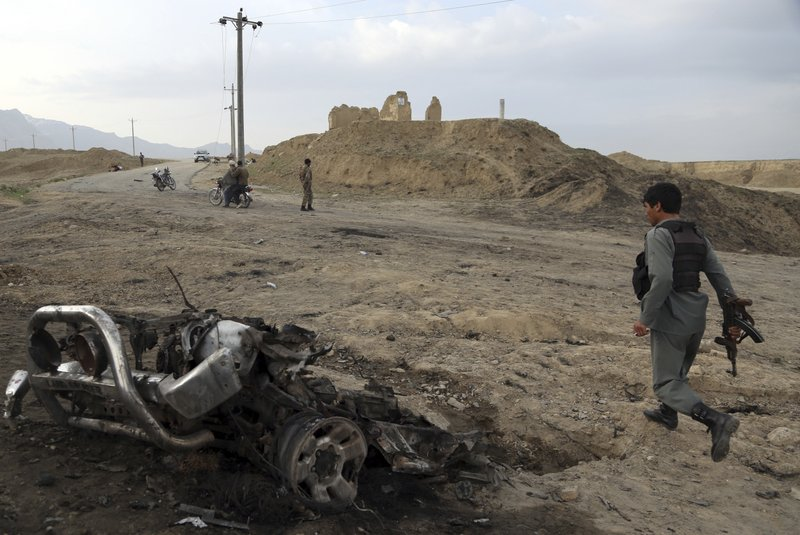 Afghan security forces gather at the site of Monday's attack near the Bagram Air Base, north of Kabul, Afghanistan, Tuesday, April 9, 2019. (AP Photo/Rahmat Gul)