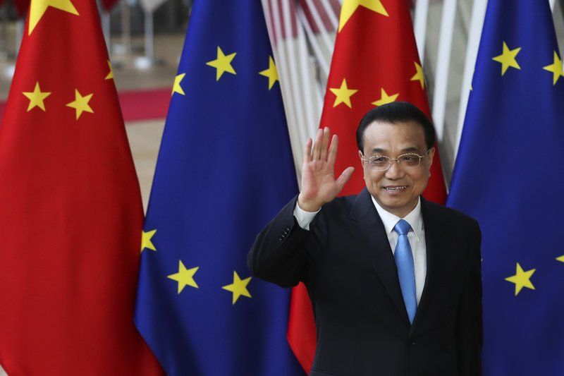 China's Prime Minister Li Keqiang gestures to the media as he is welcomed by European Council President Donald Tusk during an EU-China summit at the European Council headquarters in Brussels, Tuesday, April 9, 2019. (AP Photo/Francisco Seco)