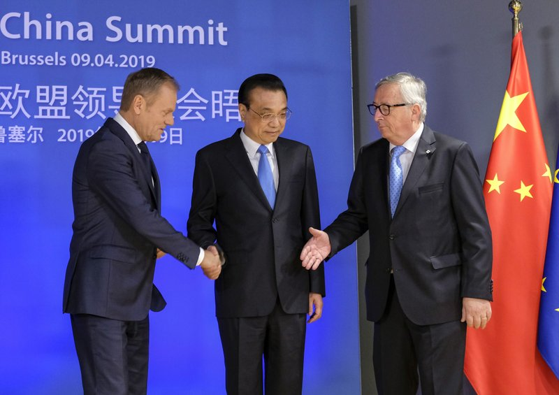 Chinese Premier Li Keqiang, center, is welcomed by European Council President Donald Tusk, left, and European Commission President Jean-Claude Juncker ahead of an EU China Summit at the European Council building in Brussels, Tuesday, April 9, 2019. (Olivier Hoslet, Pool Photo via AP)