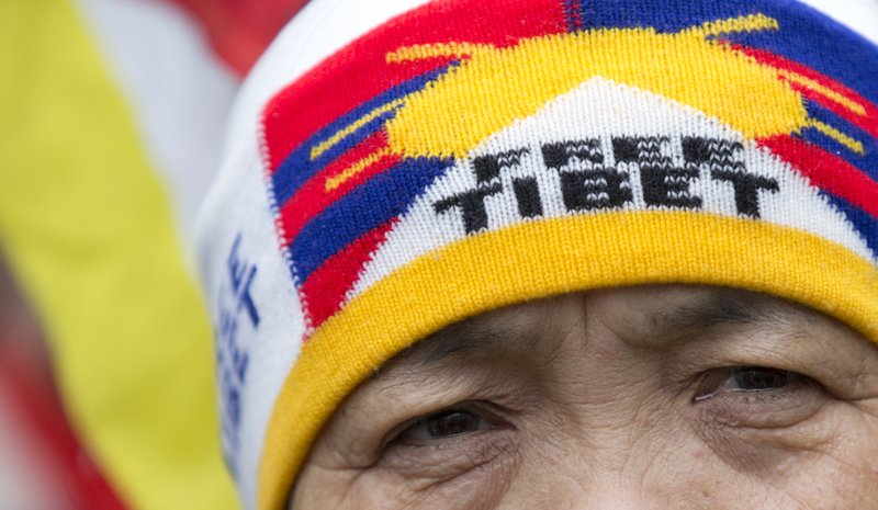 A woman wears a headband as she demonstrates for the rights of the Tibetan and Uyghur people in front of EU headquarters in Brussels ahead of an EU-China summit, Tuesday, April 9, 2019. (AP Photo/Virginia Mayo)