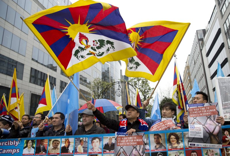 People demonstrate for the rights of the Tibetan and Uyghur people in front of EU headquarters in Brussels ahead of an EU-China summit, Tuesday, April 9, 2019. (AP Photo/Virginia Mayo)