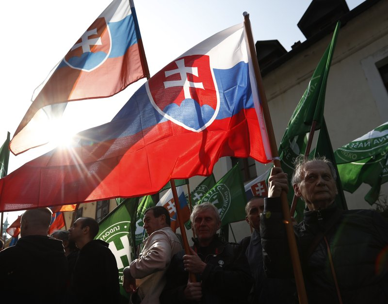 Supporters of the far right Kotleba - People's Party Our Slovakia, wave their party and Slovakia national flags outside the Supreme Court in Bratislava, Slovakia, Tuesday, April 9, 2019. (AP Photo/Petr David Josek)