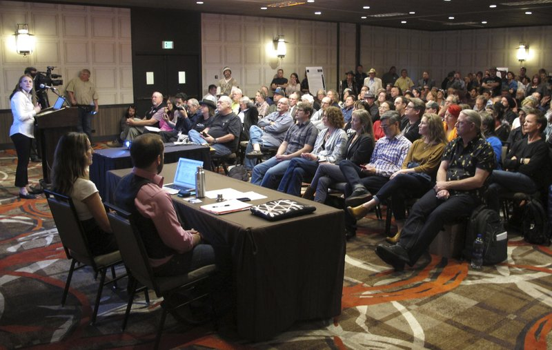 In this Monday, April 8, 2019, photoHolly Prohaska, at podium left, a project manager for a Bureau of Land Management contractor that helped prepare a draft environmental impact statement for the Burning Man festival, describes the document during a public hearing in Sparks, Nev. (AP Photo/Scott Sonner)