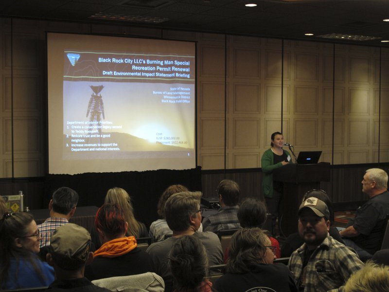 Chelsea McKinney, outdoor recreation coordinator for the U.S. Bureau of Land Management in Nevada, describes a draft environmental impact statement for the Burning Man event during a meeting in Sparks, Nev. (AP Photo/Scott Sonner)
