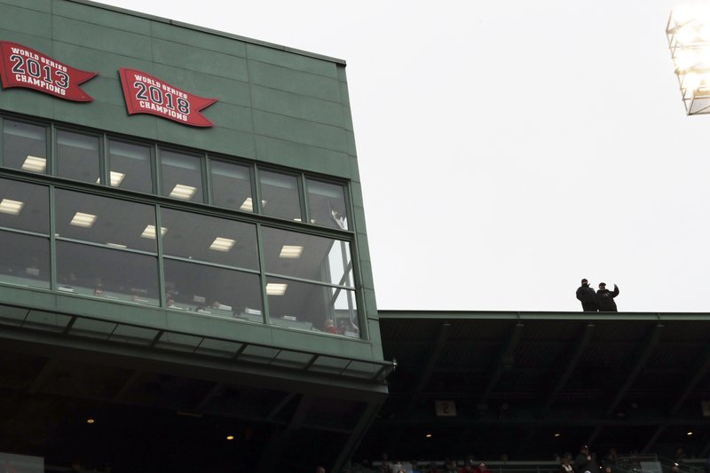 Police provide security on the roof of Fenway Park alongside the 2018 World Series Champions banner affixed to the press box before the home opener baseball game between the Boston Red Sox and the Toronto Blue Jays, Tuesday, April 9, 2019, in Boston. (AP Photo/Charles Krupa)