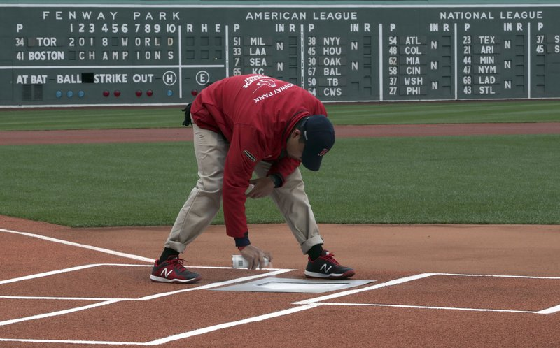 A member of the grounds crew puts fresh white paint on home plate in Fenway Park before the home opener baseball game between the Boston Red Sox and the Toronto Blue Jays, Tuesday, April 9, 2019, in Boston. (AP Photo/Charles Krupa)