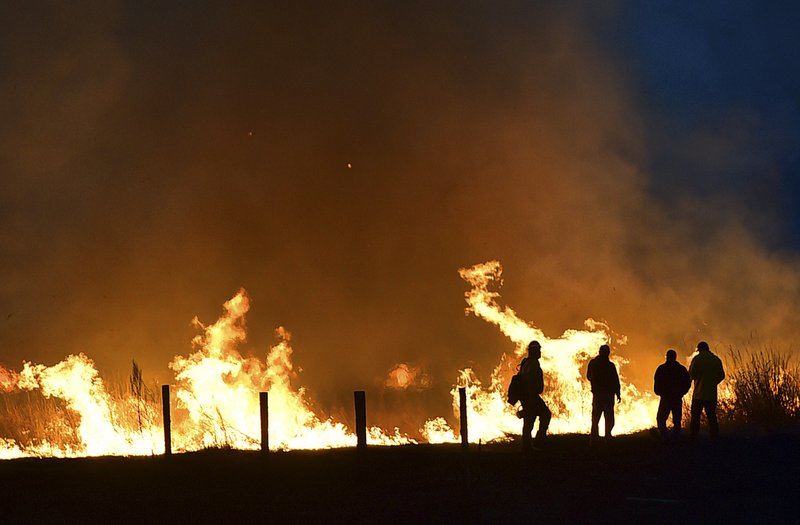 In this Sunday April 7, 2019 photo, residents watch as a fire races across a field on the edge of town in Lame Deer, Mont. (Larry Mayer/Billings Gazette via AP)