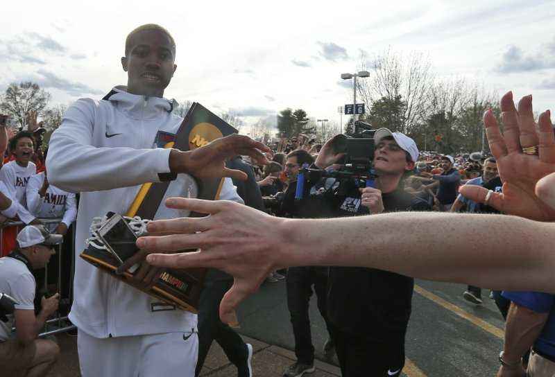Mamadi Diakite hoods the NCAA championship trophy as Virginia team members are welcomed by fans as they return to Charlottesville, Va. (AP Photo/Steve Helber)