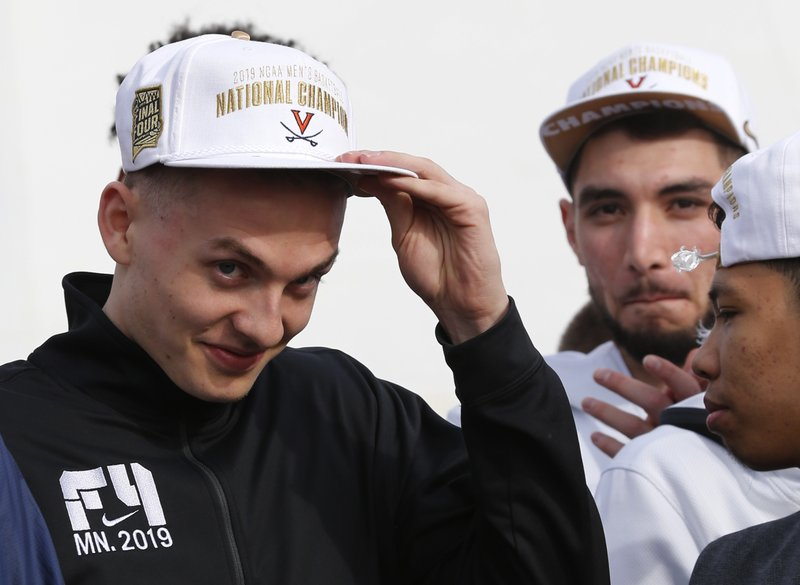 Tournament MVP Kyle Guy adjusts his hat as he is introduced during a welcoming ceremony as he and members of the Virginia basketball team are welcomed by fans as they return home after their win of the championship in the Final Four NCAA college basketball tournament against Texas Tech, in Charlottesville, Va. (AP Photo/Steve Helber)