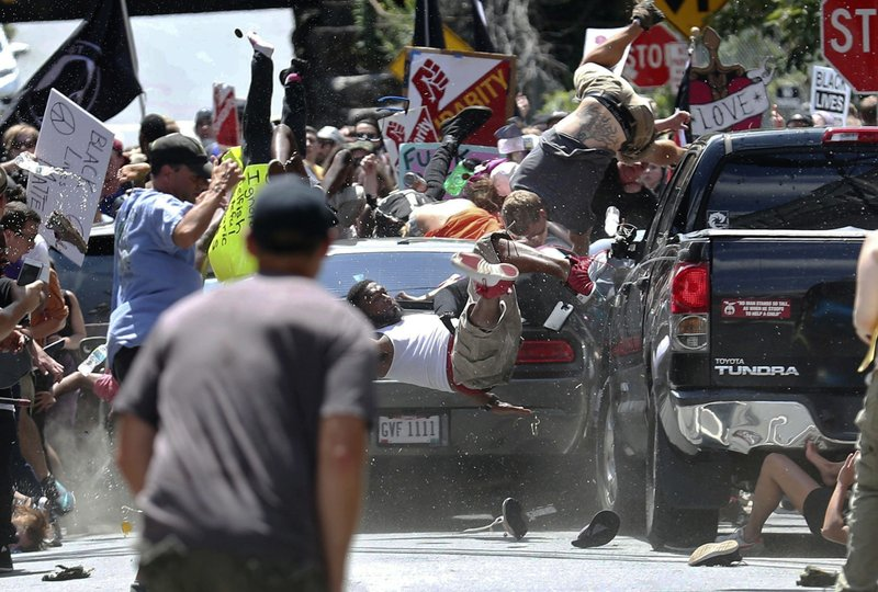 FILE - In this Aug. 12, 2017, file photo, people fly into the air as a vehicle is driven into a group of protesters demonstrating against a white nationalist rally in Charlottesville, Va. (Ryan M. Kelly/The Daily Progress via AP, File)