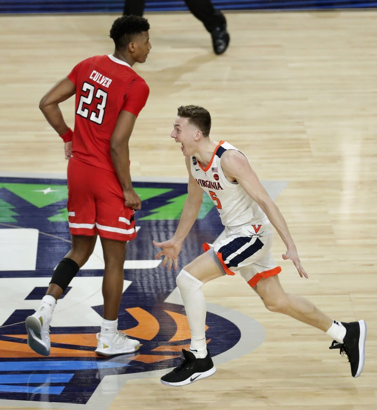 Virginia guard Kyle Guy celebrates in front of Texas Tech guard Jarrett Culver (23) at the end of the the championship game in the Final Four NCAA college basketball tournament, Monday, April 8, 2019, in Minneapolis. (AP Photo/Matt York)