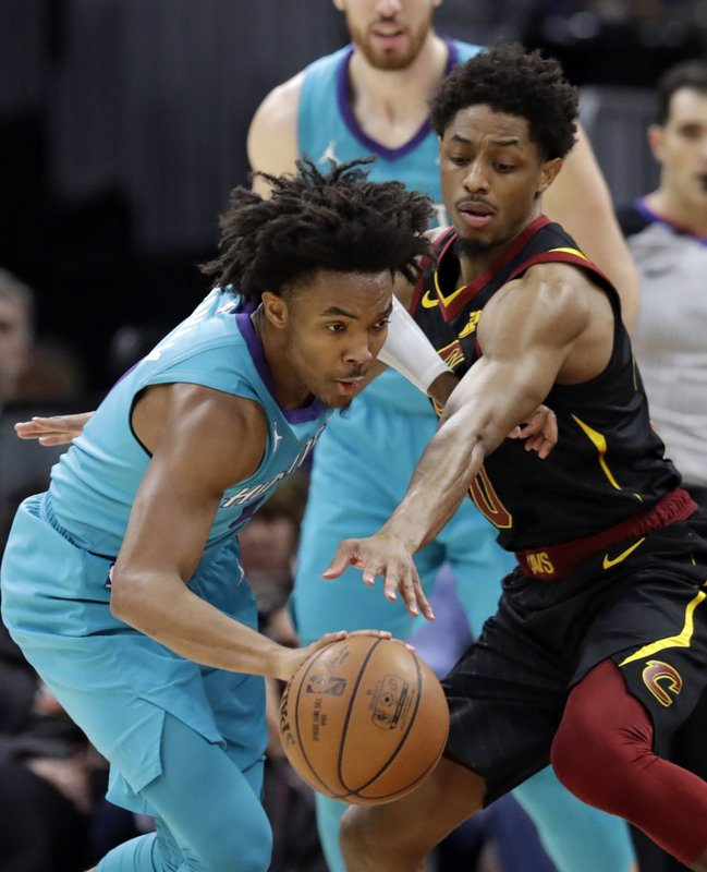 Charlotte Hornets' Devonte' Graham, left, drives past Cleveland Cavaliers' Brandon Knight in the first half of an NBA basketball game, Tuesday, April 9, 2019, in Cleveland. (AP Photo/Tony Dejak)