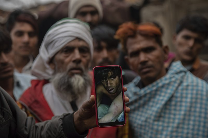 FILE- In this Jan. 22, 2019 file photo, a man holds a phone showing a video of Muslim farmer moments after being beaten for allegedly smuggling cows in Mirzapur, India. (AP Photo/Bernat Armangue)