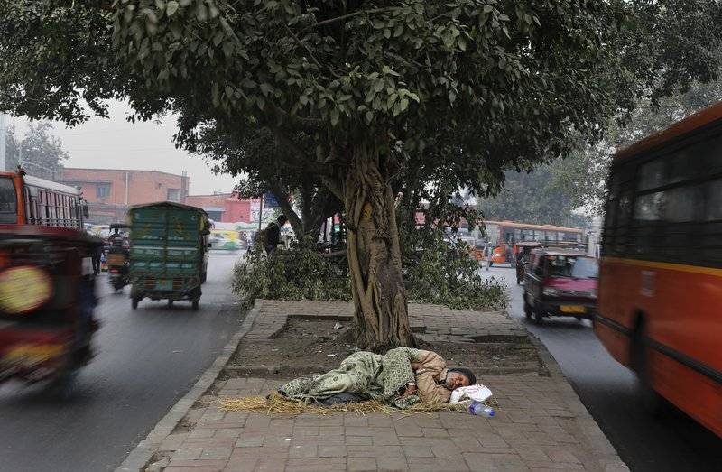 FILE- In this Jan. 16, 2019, file photo, a homeless man sleeps on a median strip in New Delhi, India. ($85) annually, benefiting as many as 120 million households and income tax relief to the middle class. (AP Photo/Altaf Qadri, File)