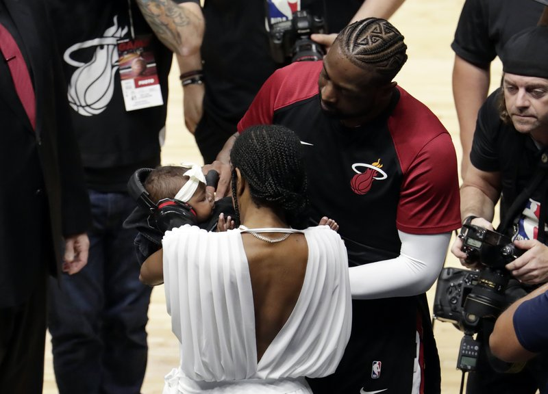 Miami Heat guard Dwyane Wade greets his daughter Kaavia James, and wife Gabrielle Union before a pregame ceremony honoring Wade, who is playing his final home regular season game when the Heat host the Philadelphia 76ers, Tuesday, April 9, 2019, in Miami. (AP Photo/Lynne Sladky)