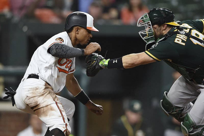 Baltimore Orioles Richie Martin is tagged out at the plate by Oakland Athletics catcher Ramon Laureano in the third inning of a baseball game, Tuesday, April 9, 2019, in Baltimore. (AP Photo/Gail Burton)