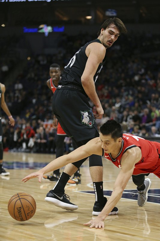 Toronto Raptors' Jeremy Lin falls to get the ball behind Minnesota Timberwolves' Dario Saric in the first half of an NBA basketball game Tuesday April 9, 2019, in Minneapolis. (AP Photo/Stacy Bengs)