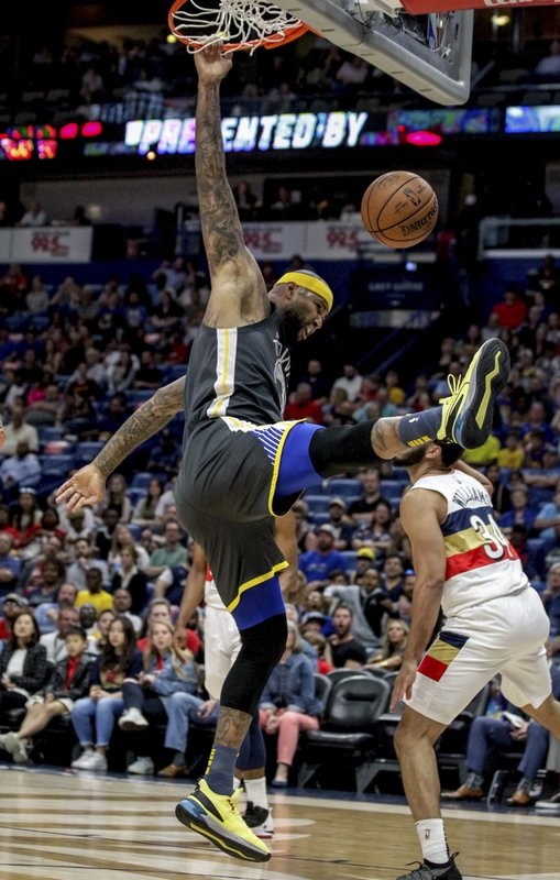 Golden State Warriors center DeMarcus Cousins (0) dunks over New Orleans Pelicans guard Kenrich Williams (34) in the first half of an NBA basketball game in New Orleans, Tuesday, April 9, 2019. (AP Photo/Scott Threlkeld)