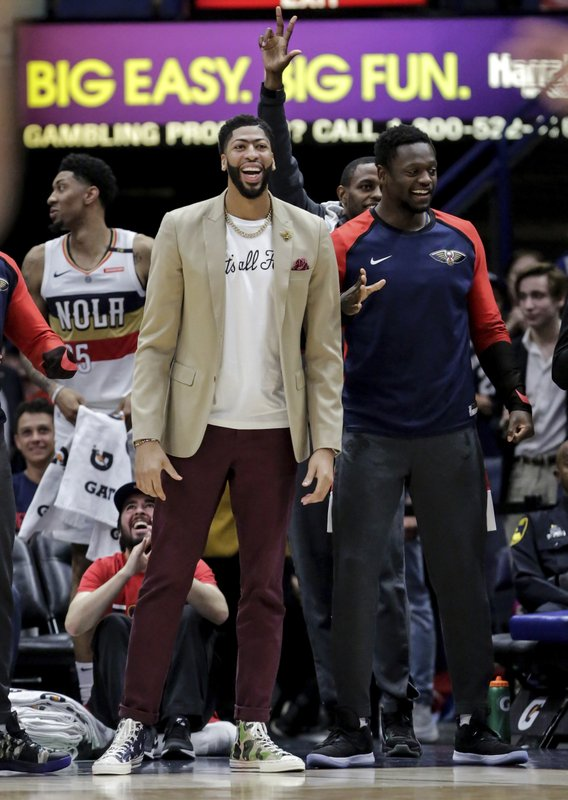 New Orleans Pelicans forward Anthony Davis, center, celebrates with teammates after forward Cheick Diallo (13) sunk a three-point basket against the Golden State Warriors in the first half of an NBA basketball game in New Orleans, Tuesday, April 9, 2019. (AP Photo/Scott Threlkeld)