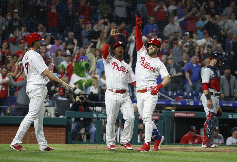 Philadelphia Phillies' Bryce Harper, center right, celebrates his three-run home run with Jean Segura, center left, and Aaron Nola, left, as Washington Nationals catcher Yan Gomes, right, waits during the third inning of a baseball game Tuesday, April 9, 2019, in Philadelphia. (AP Photo/Chris Szagola)