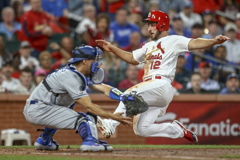 St. Louis Cardinals' Paul DeJong (12) slides home to score next to Los Angeles Dodgers catcher Austin Barnes during the third inning of a baseball gameTuesday, April 9, 2019, in St. (AP Photo/Scott Kane)