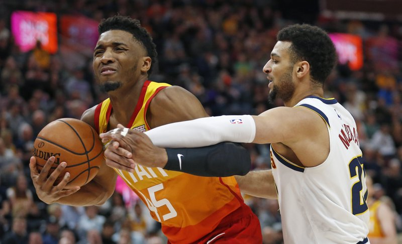 Denver Nuggets guard Jamal Murray, right, defends against Utah Jazz guard Donovan Mitchell (45) in the first half during an NBA basketball game Tuesday, April 9, 2019, in Salt Lake City. (AP Photo/Rick Bowmer)