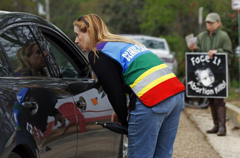 FILE - In this March 20, 2018, file photo, clinic escort Kim Gibson speaks with driver as they attempt to enter the Jackson Women's Health Organization's clinic parking lot, the only facility in the state that performs abortions in Jackson, Miss. (AP Photo/Rogelio V. Solis, File)