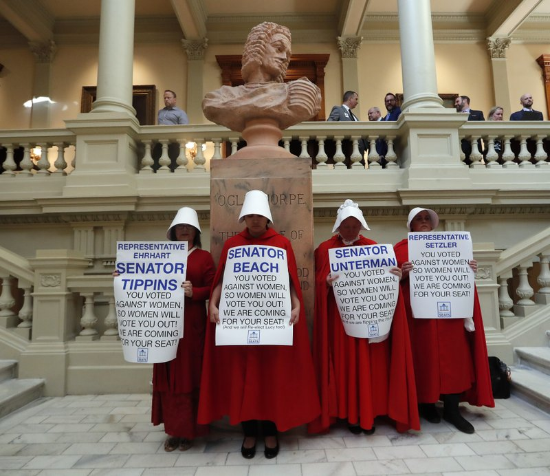 FILE - In this April 2, 2019, file photo, women hold signs to protest HB 481 at the state Capitol in Atlanta. (AP Photo/John Bazemore, File)