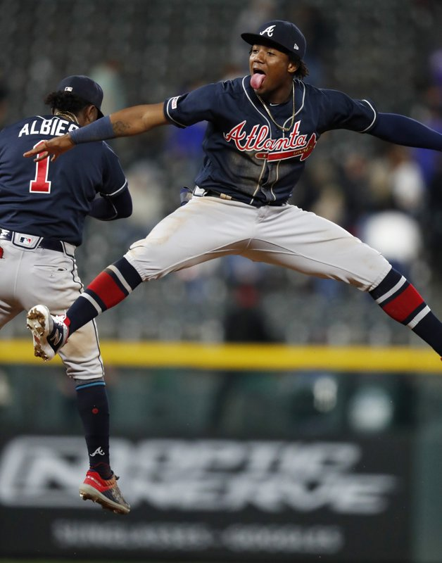 Atlanta Braves left fielder Ronald Acuna Jr., front, celebrates with second baseman Ozzie Albies after the team's baseball game against the Colorado Rockies on Tuesday, April 9, 2019, in Denver. (AP Photo/David Zalubowski)