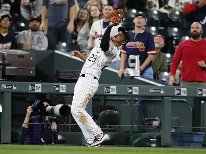 Colorado Rockies third baseman Nolan Arenado pulls in a pop foul by Atlanta Braves' Josh Donaldson for the final out in the top of the ninth inning of a baseball game Tuesday, April 9, 2019, in Denver. (AP Photo/David Zalubowski)