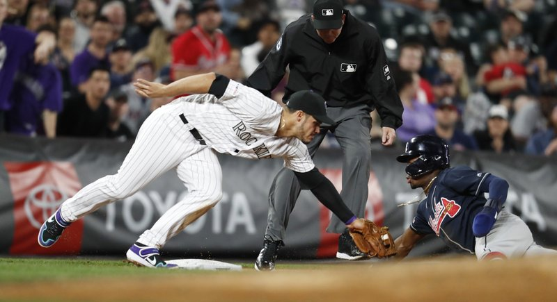 Colorado Rockies third baseman Nolan Arenado, left, tags out Atlanta Braves' Ronald Acuna Jr., who tried to advance from second to third on a passed ball during the eighth inning of a baseball game Tuesday, April 9, 2019, in Denver. (AP Photo/David Zalubowski)